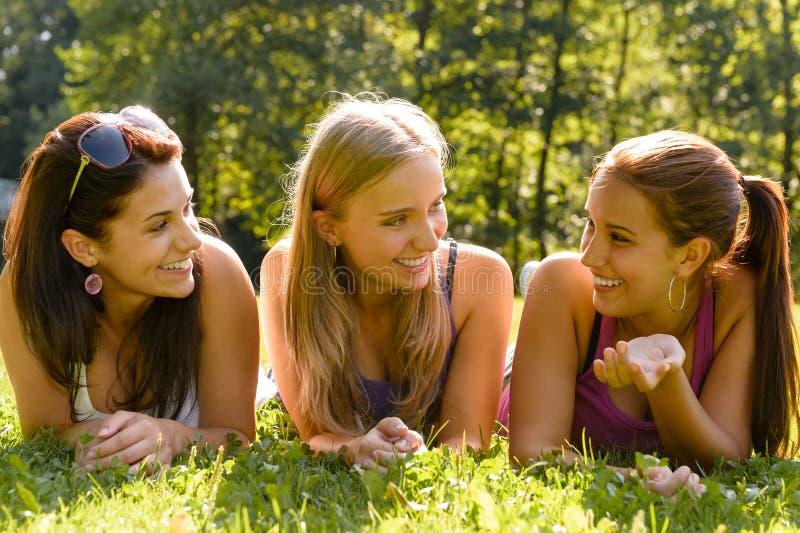 联系和放松在公园的青少年的妇女 免版税库存照片