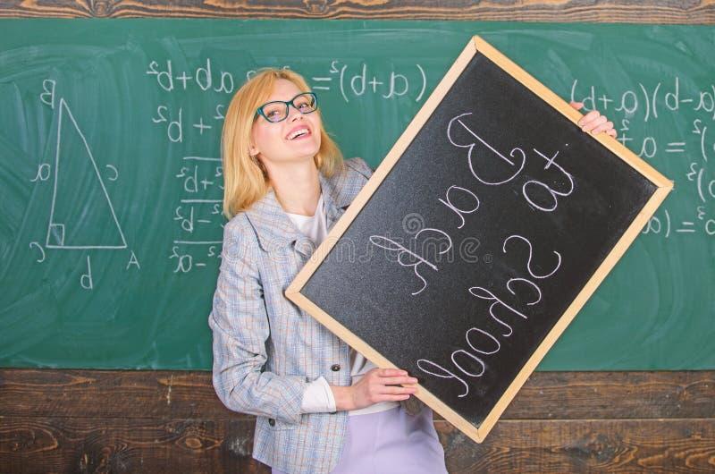 聘用的老师新的学年 妇女老师拿着黑板题字回到学校 看做 免版税图库摄影