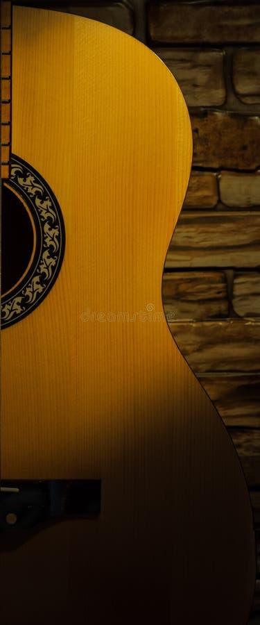 聚光灯照亮的声学吉他对砖墙 图库摄影