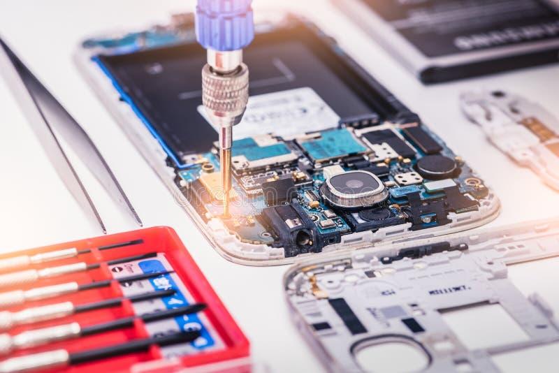 聚集在智能手机里面的技术员的抽象图象由螺丝刀在实验室里 免版税库存图片