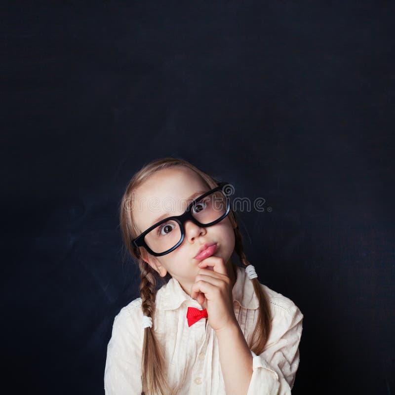 聪明儿童认为 玻璃的小女孩在粉笔板 免版税库存照片