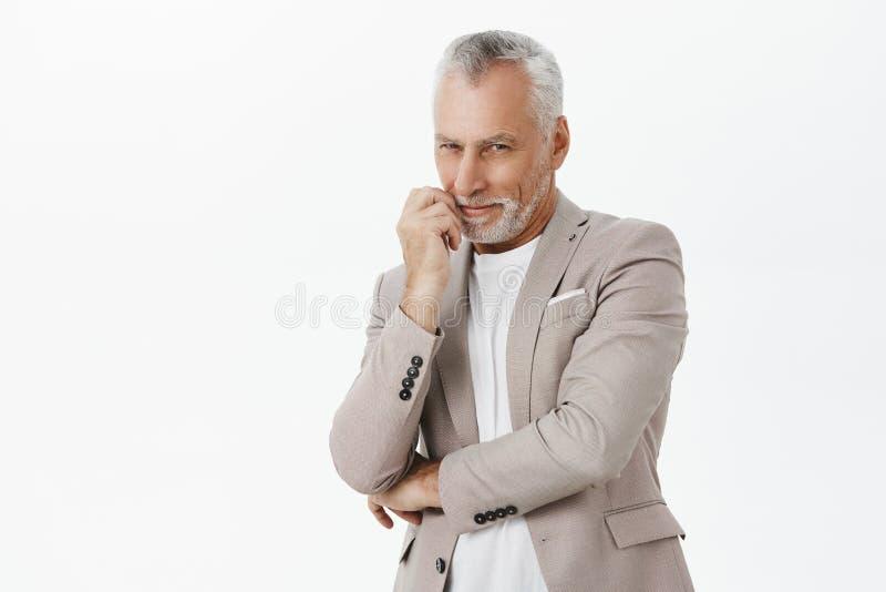 聪明和棘手的热心老人用白色胡须和头发反对胸口和接触嘴唇微笑的横穿手 库存图片