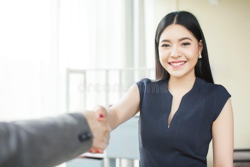 聪明和确信的亚裔女实业家微笑和与其它事项伙伴握手 免版税库存图片