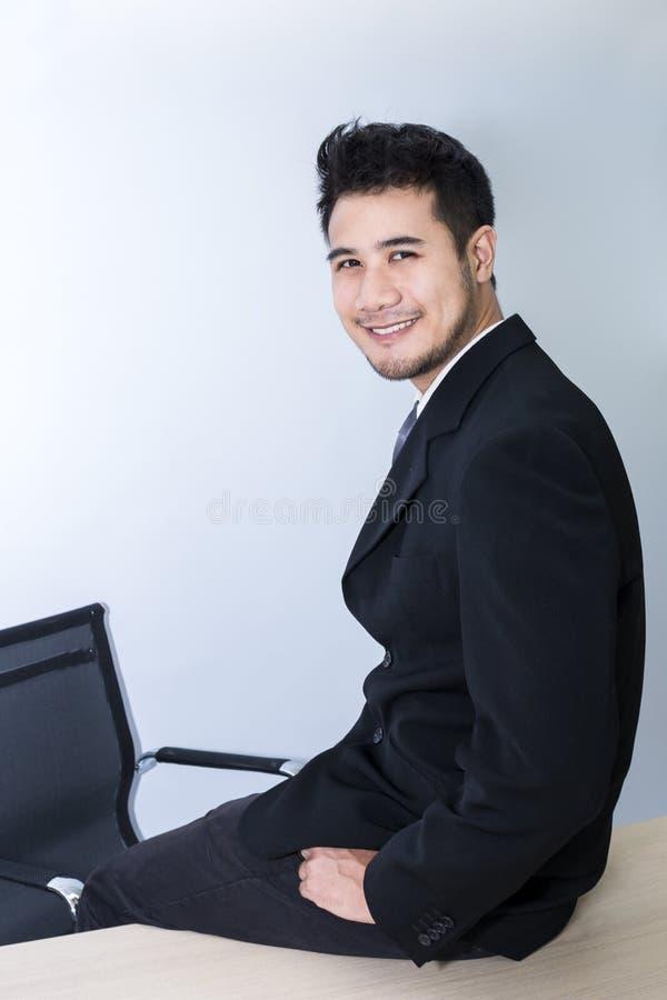 聪明年轻英俊的商人微笑和坐桌在办公室 免版税库存图片
