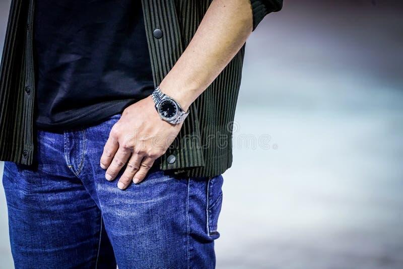 聪明的人摆在与他的手表、衣服和斜纹布 关闭在他的手和手表 免版税库存图片