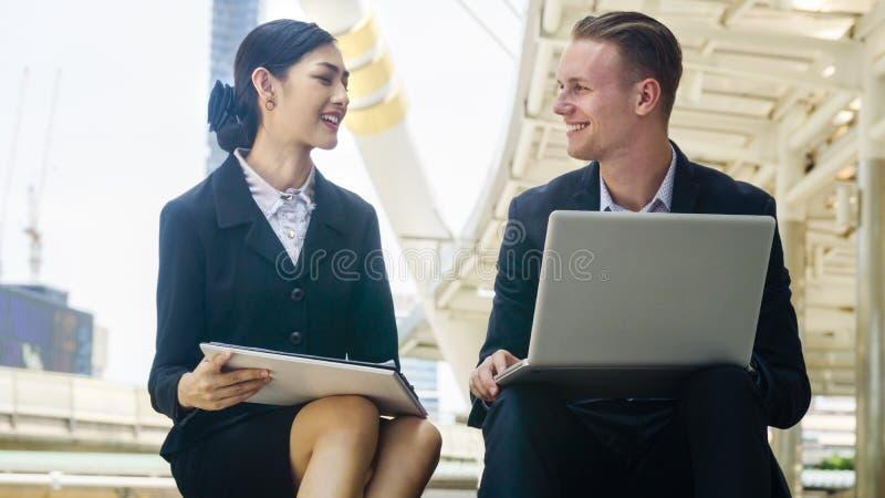 聪明的企业白种人男人和亚洲秘书妇女坐 免版税库存照片