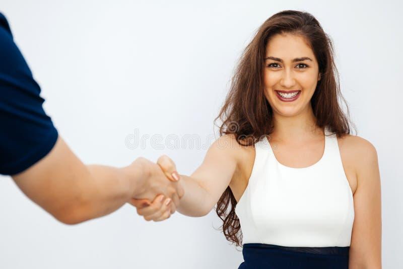 聪明的便服的美丽的女商人与男性同事握手 免版税图库摄影