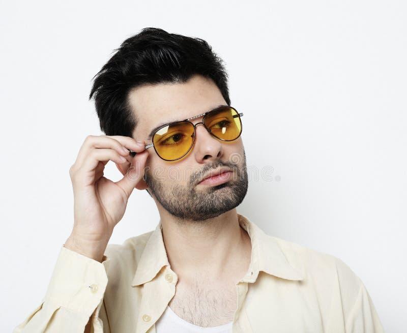 聪明的便衣和太阳镜的典雅的年轻帅哥 演播室时尚画象 库存照片