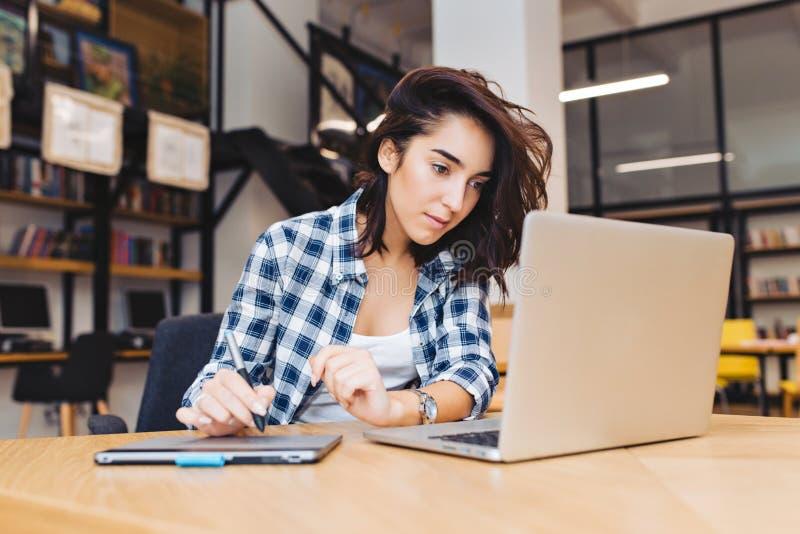 聪明的俏丽的年轻女人与在桌上的膝上型计算机一起使用在图书馆里 学习在大学,学会,自由职业者,工作 库存照片