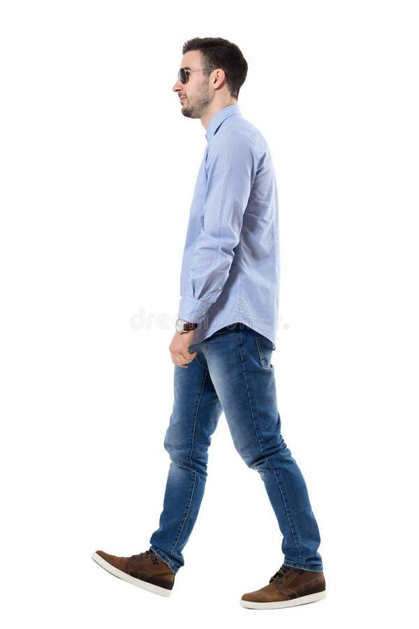 年轻聪明的偶然商人走的佩带的太阳镜侧视图  免版税库存照片