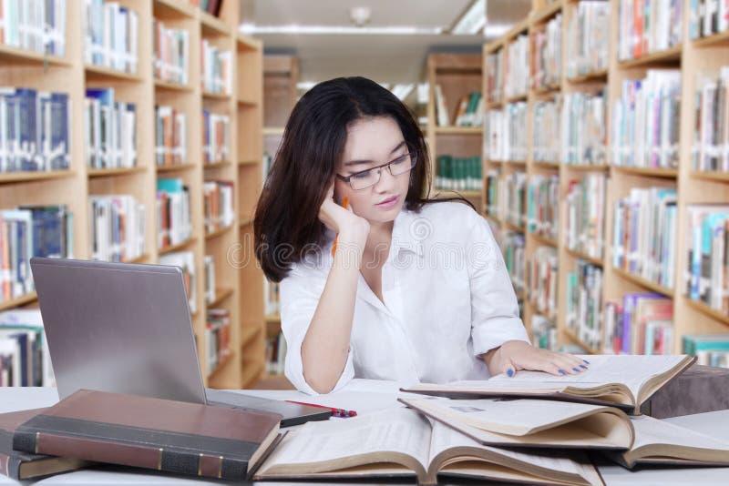 download 聪明的女学生在图书馆里读书 库存照片.