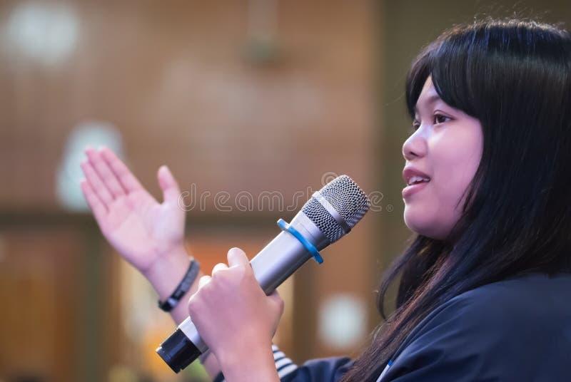 聪明的女实业家讲话或讲话与话筒在研讨会大厅,打手势解释的手里抗议或信仰  库存照片