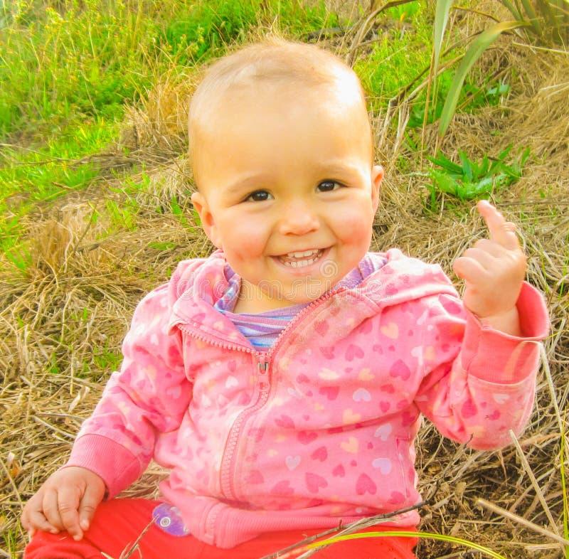 聪明的女婴举她的手指 免版税库存照片