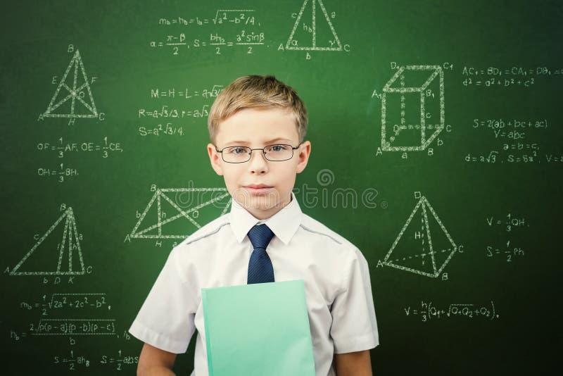 聪明的学生或男小学生有站立近的黑板的笔记本的 库存图片