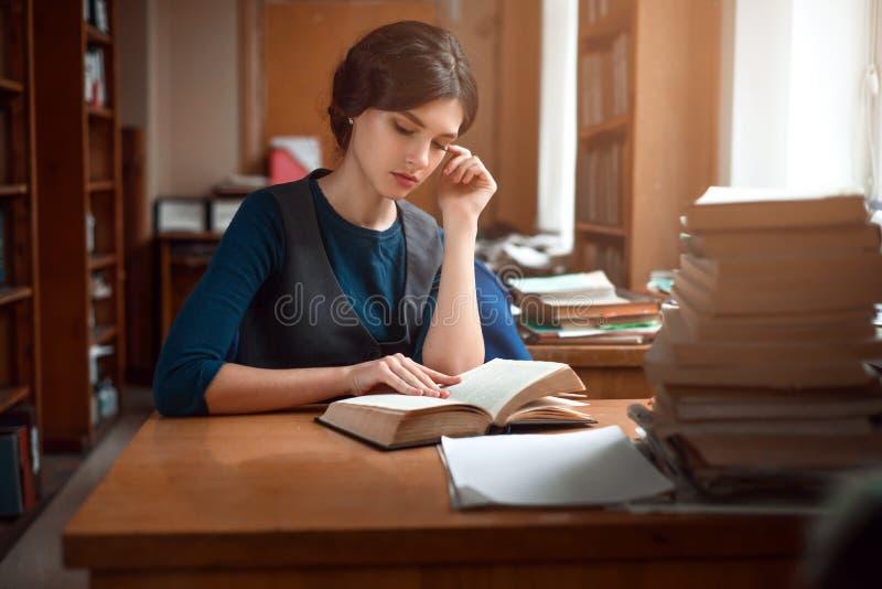 聪明的学生画象在大学图书馆里 免版税库存照片