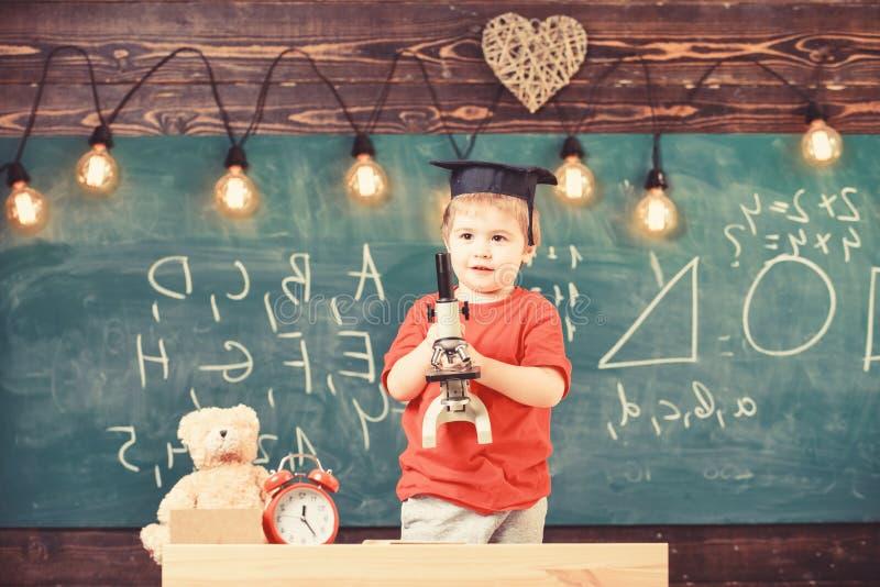 聪明的孩子概念 第一前对学习感兴趣,学会,教育 愉快的面孔的孩子拿着显微镜 ?? 免版税库存照片