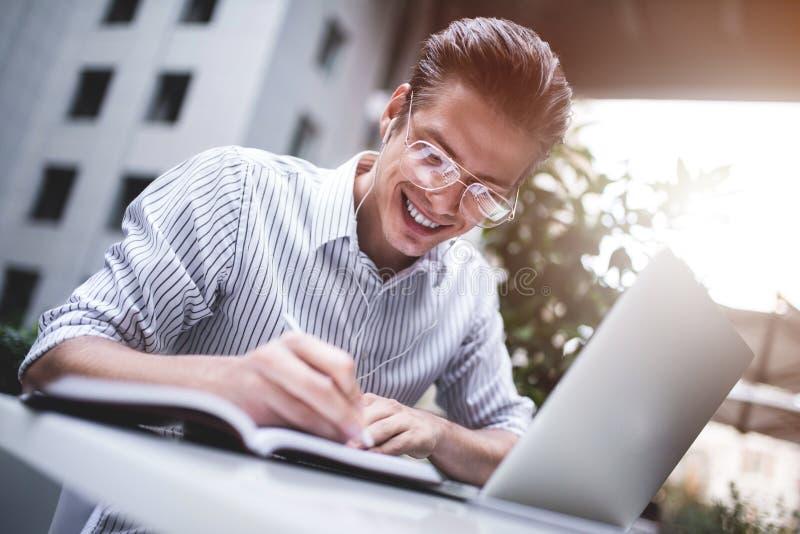 聪明的态度 使用膝上型计算机的正面英俊的人和坐在咖啡馆,当浏览互联网时 年轻博客作者或journali 免版税库存照片