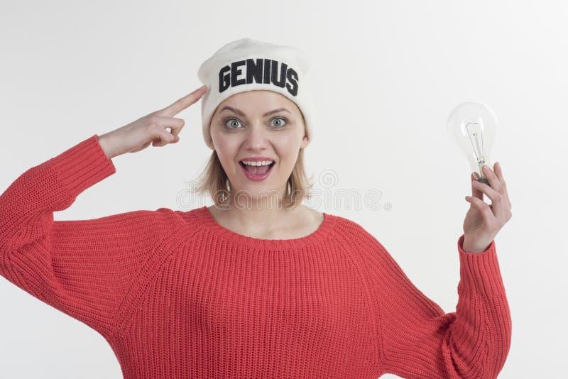 聪明的是新性感 女孩天才有明亮的想法 指向头的愉快的妇女举行电灯泡 肉欲的女服 免版税图库摄影