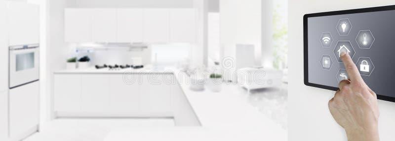 聪明的有标志的家庭自动化手接触数字片剂屏幕在户内室和厨房背景、网横幅和拷贝 免版税库存图片