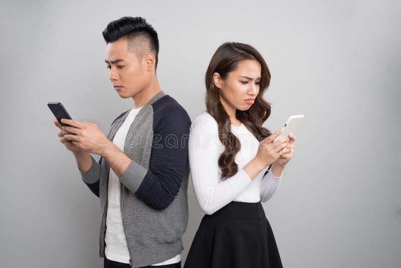 聪明的电话瘾概念 使用互联网的年轻亚洲夫妇 免版税库存图片
