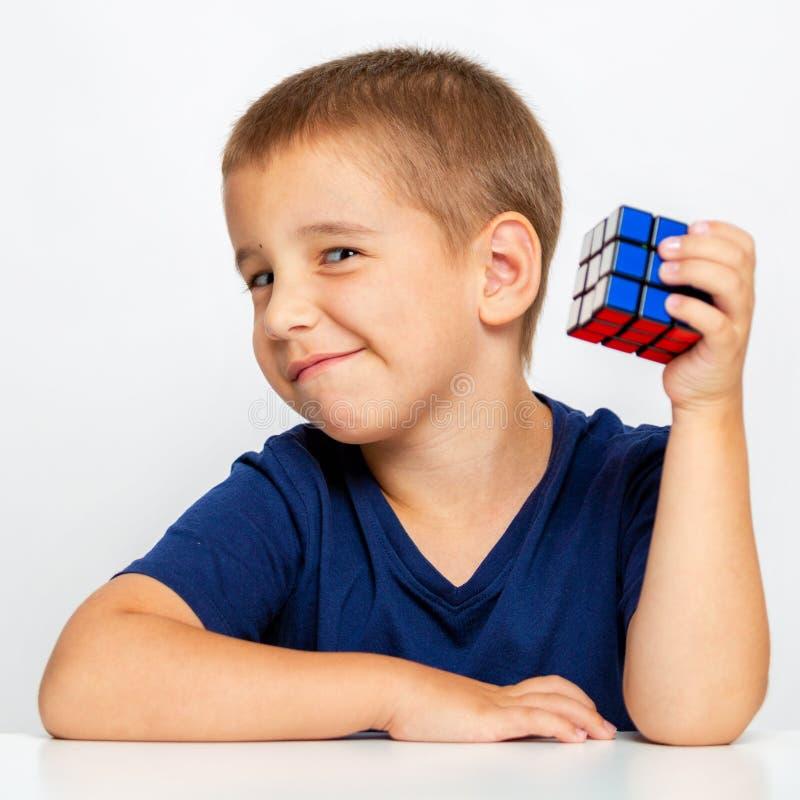 聪明的男孩 孩子解决了问题 他收集了Rubik ` s立方体 免版税库存照片