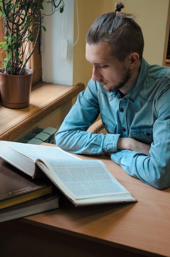 聪明的男性行家学生阅读书和开会在桌上在公立大学图书馆里 侧视图被射击  免版税库存图片
