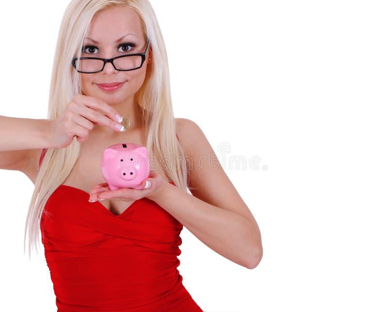 聪明的白肤金发的少妇节省额货币在查出的存钱罐中 免版税图库摄影