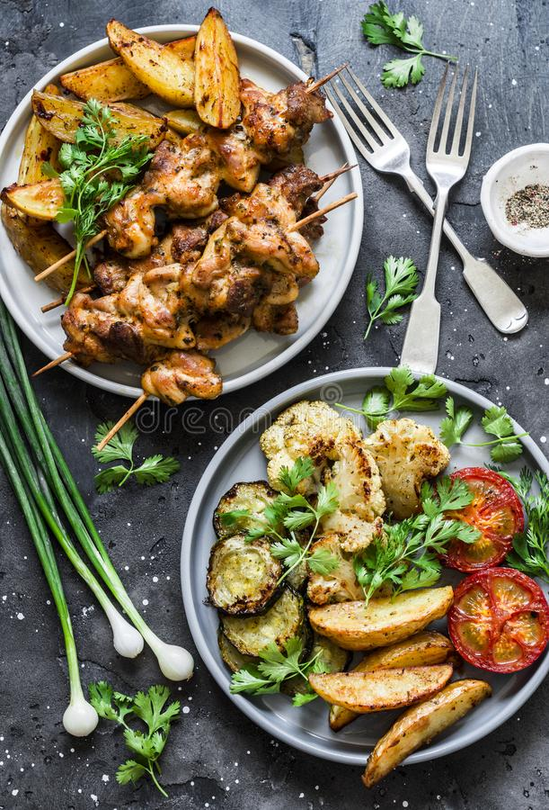 肉串kebab用被烘烤的土豆和烤夏南瓜,蕃茄,在黑暗的背景的花椰菜,顶视图 可口塔帕纤维布 免版税库存照片