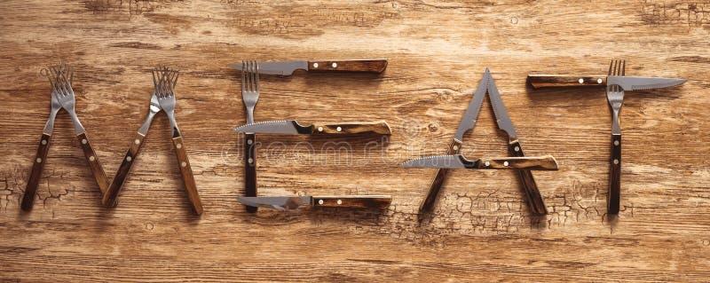 肉写与叉子和刀子利器在土气木桌 库存照片