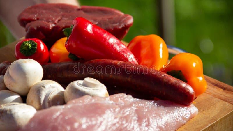 肉和菜在准备好一块木的板材烤肉 库存照片