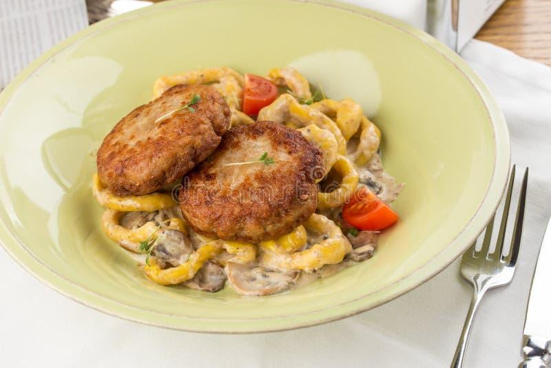 肉小馅饼用蘑菇和意粉在白色纺织品桌上 免版税库存图片