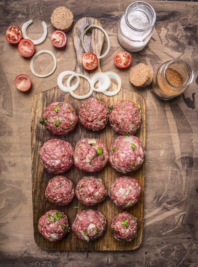 肉末球在一个切板的有西红柿和调味料木土气背景顶视图关闭的 免版税图库摄影
