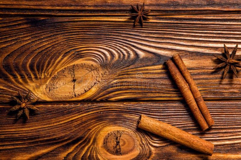 肉桂条和星状茴香位于棕色木板 免版税库存图片