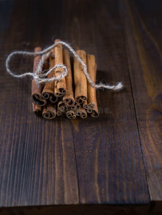 肉桂条栓与在老木背景的黄麻绳索在土气样式 免版税库存照片