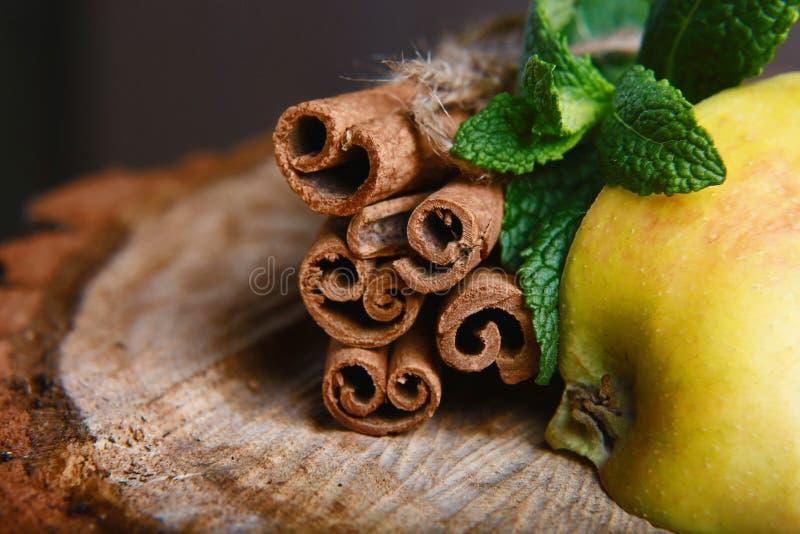 肉桂条栓了和裁减苹果,在木背景的绿色新鲜薄荷 选择聚焦 免版税库存照片