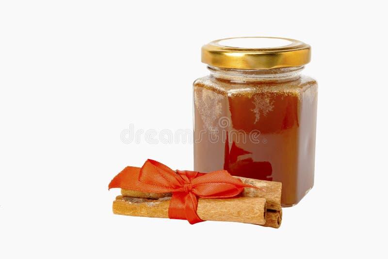 肉桂,白色背景上加一罐蜂蜜 免版税库存图片
