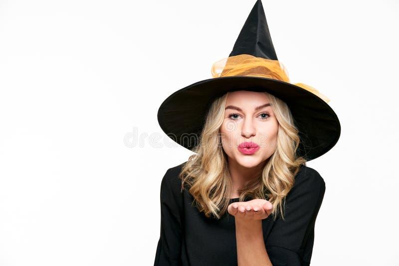 肉欲的万圣夜巫婆演播室画象 可爱的少妇在巫婆送往照相机的万圣夜服装穿戴了一个飞吻 免版税库存照片