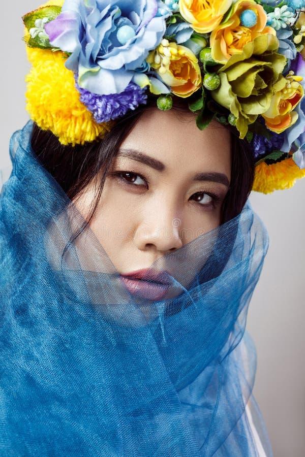 肉欲的亚裔美女和在浅灰色的背景,特写镜头的蓝色面纱画象有花卉帽子的 免版税图库摄影