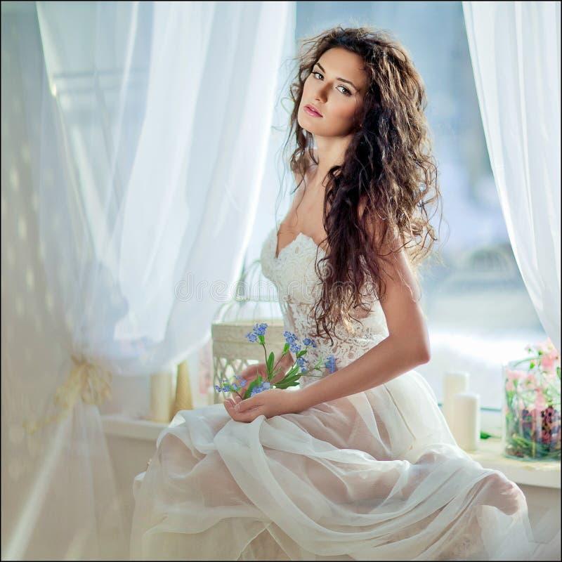 肉欲的卷发的女孩画象一件白色礼服的反对t 库存照片