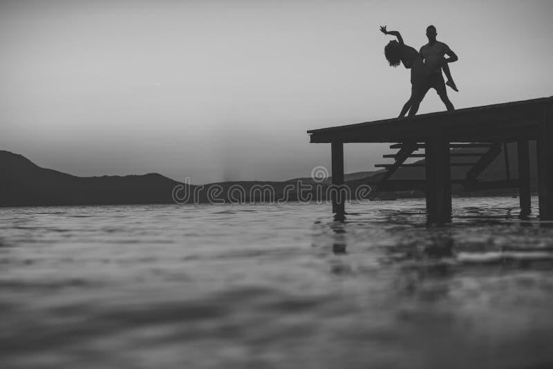 肉欲的夫妇跳舞剪影在码头的有在海表面上的日落的在背景 拉丁文和爱概念 免版税图库摄影