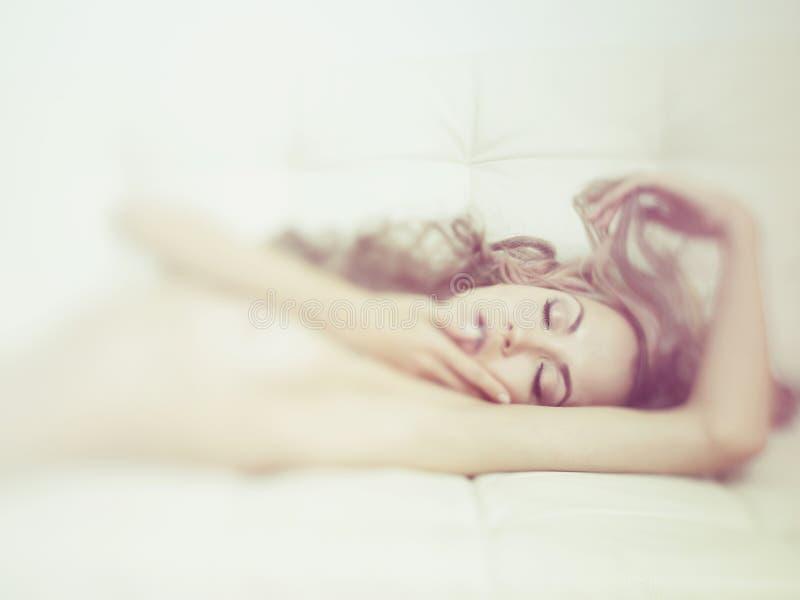 肉欲的妇女在床上 免版税库存照片