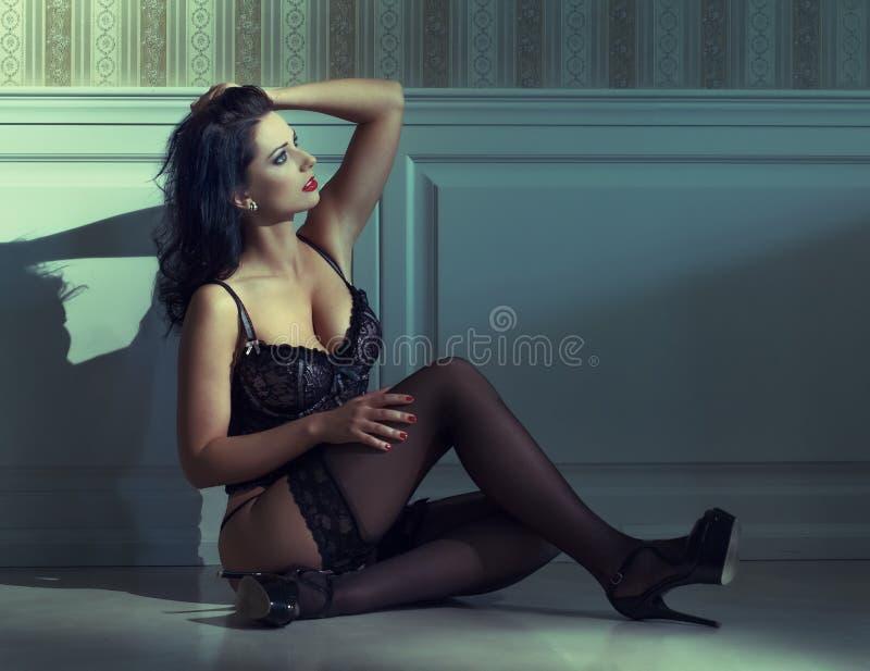 肉欲的妇女坐地板在晚上 免版税库存图片