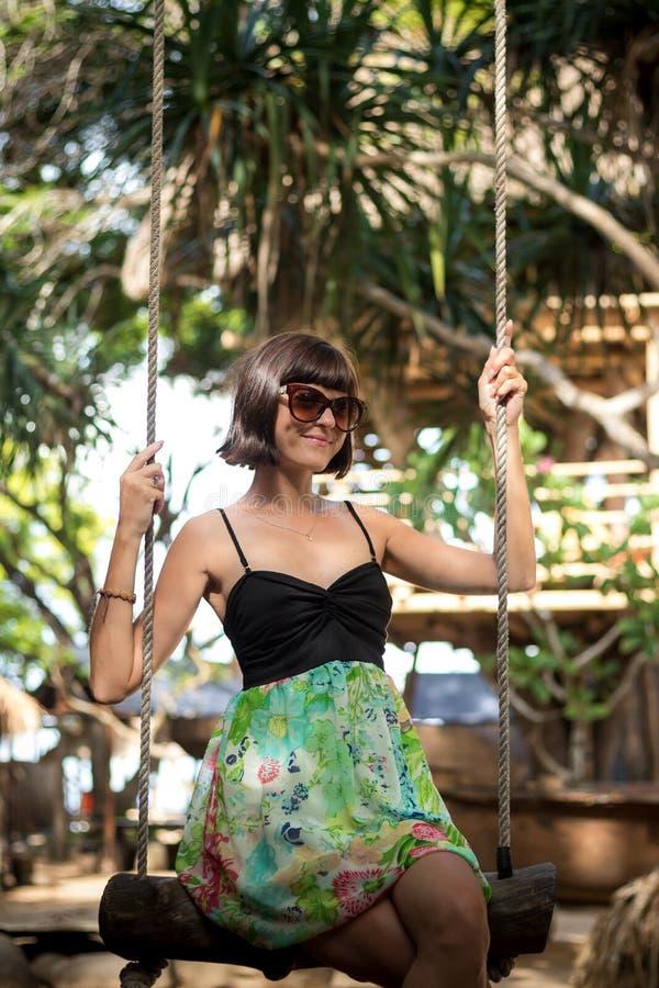 肉欲的嫩女孩坐穿美丽的礼服的摇摆 她有长的黑发 摇摆在海滩与 库存图片