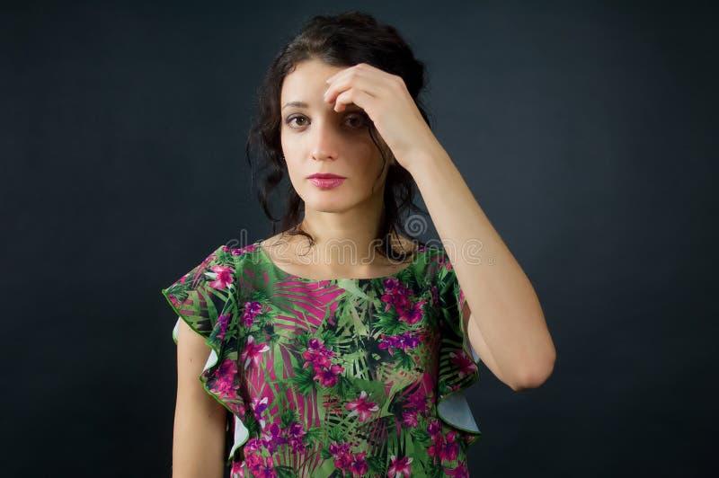 肉欲的少女女性画象绿色礼服的有摆在黑背景的演播室的桃红色花的 免版税库存照片