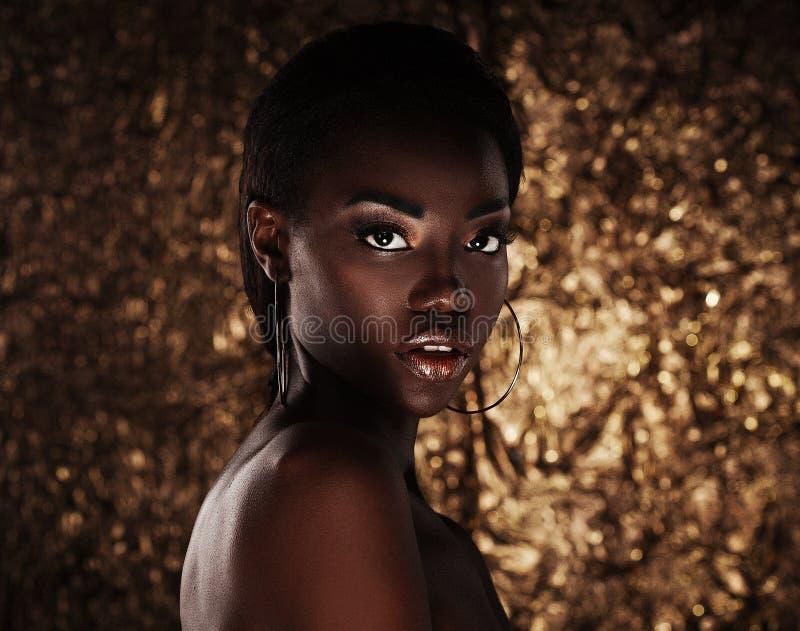 肉欲的年轻非洲妇女画象反对金黄背景的 免版税图库摄影