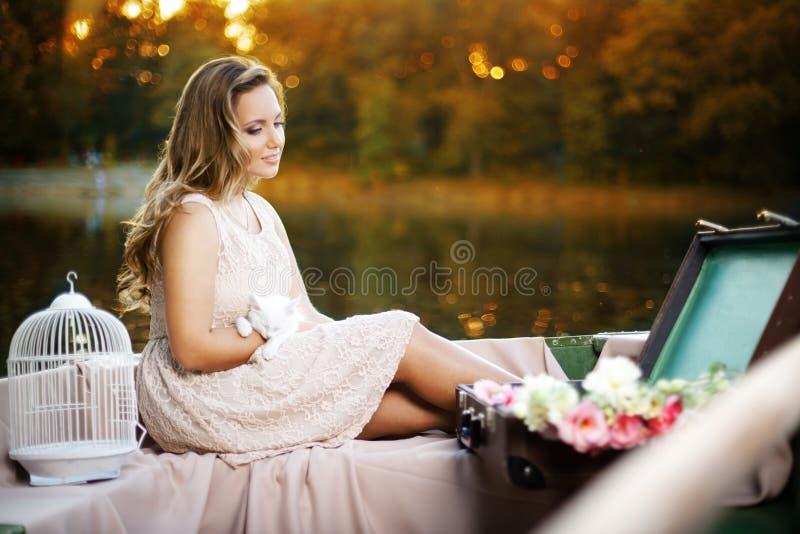 肉欲的浪漫女孩档案,穿戴在夏天礼服,供以座位在有小猫的小船在手上,在日落光期间 免版税库存图片