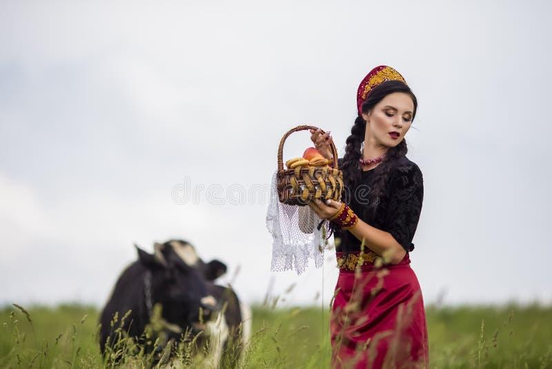 肉欲的白种人浅黑肤色的男人画象俄国Kokoshnik的与面包圆环篮子  摆在反对母牛在领域户外 免版税库存照片