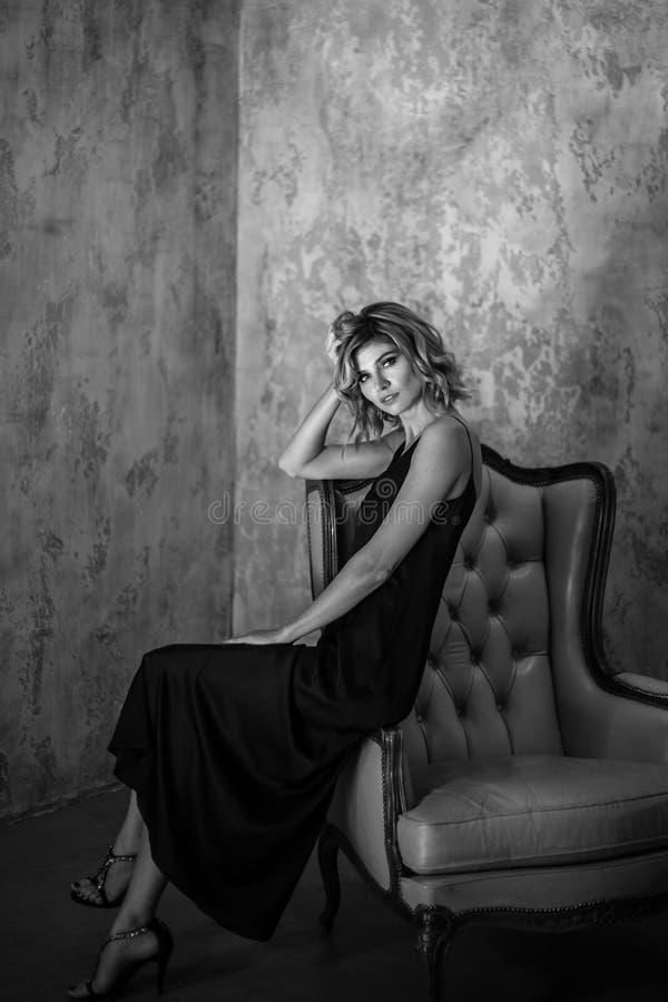 肉欲的白肤金发的妇女,时尚在内部的秀丽照片画象一件长的丝绸晚礼服的 库存照片