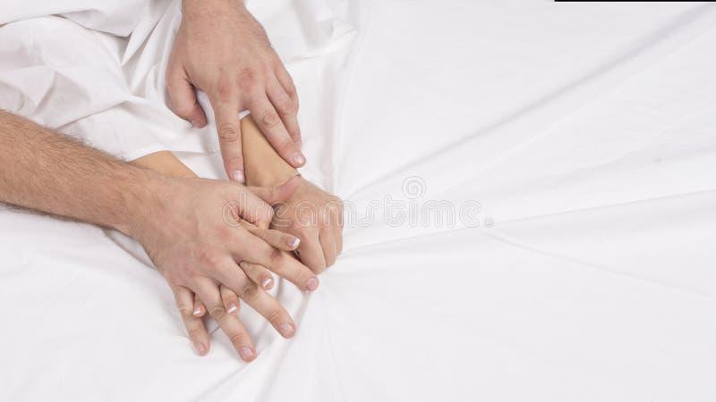 肉欲的美好的年轻夫妇有在床上的性 拉扯在销魂,性交高潮的女性手白色板料 概念亲吻妇女的爱人 免版税图库摄影
