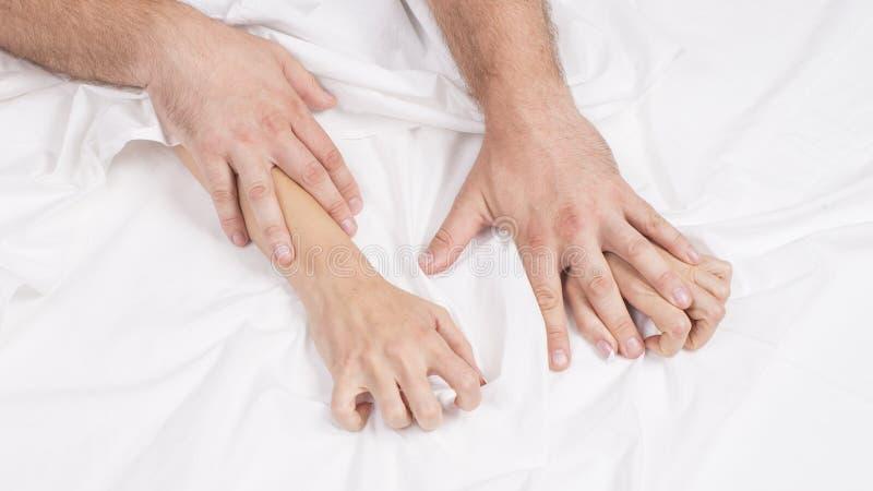 肉欲的美好的年轻夫妇有在床上的性 拉扯在销魂,性交高潮的女性手白色板料 概念亲吻妇女的爱人 图库摄影
